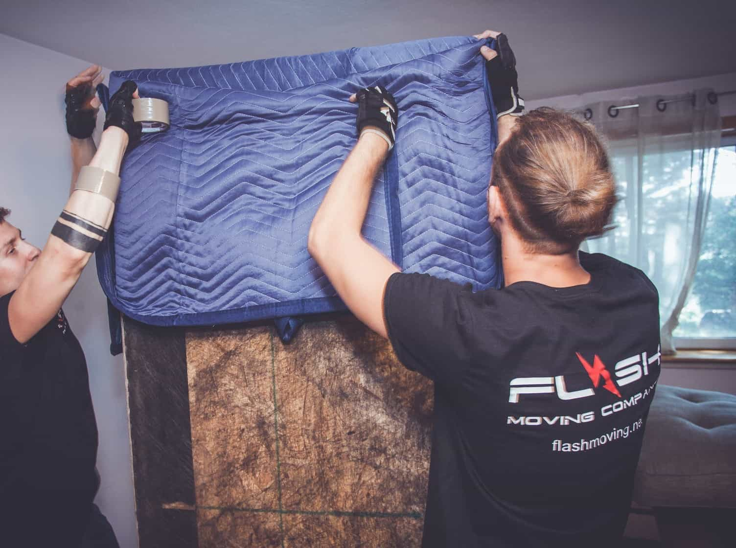 This image shows Flash Moving crew werapping a piece of furniture for a local move.